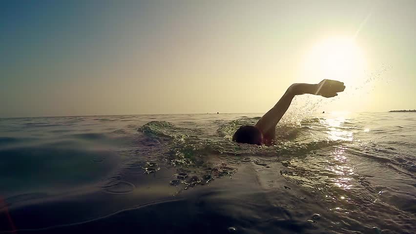 Professional sport man swim crawl in sea at sunset, cinematic slow motion trekking shot | Shutterstock HD Video #1009014536