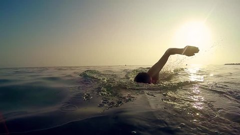 Professional sport man swim crawl in sea at sunset, cinematic slow motion trekking shot