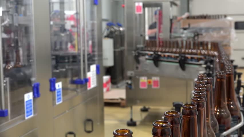 Automatic Beer Bottling Line. Queue of empty bottles on the conveyor. | Shutterstock HD Video #1009015136