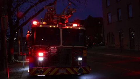 Fire truck with flashing red and white lights responds to a fire emergency in the city at night time. Blinking lights from a first responder fire engine.