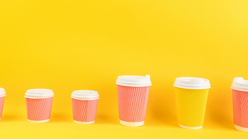 moving in a row of family cups for coffee. Adults and children. Large and small size. Video footage funny timelapse stop motion. Yellow bright background. yellow and pink colors