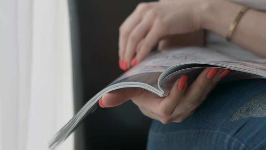 Woman Hands holding open holding magazine. Close up