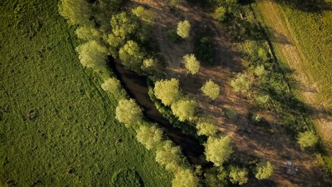 Rural English river, Suffolk. Aerial video footage looking vertically down and following the meandering route of a tree lined river rolling through the heart of the Suffolk countryside.