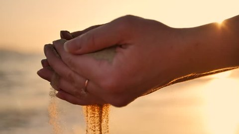 Sand running through a womans hands