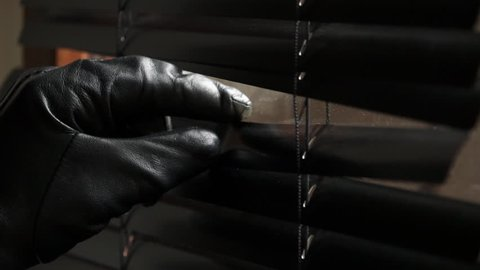 Black leather glove spreading black panels of window blind to look outside. Peeping through window blind to see what's happening outside.