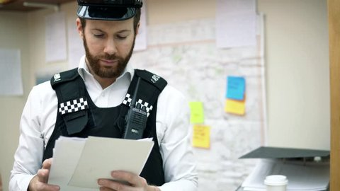 Portrait Of A Uniform Police Officer Cop At Police Station, Briefing 4K. White Caucasian With Beard. Takes Off Hat. Serious And Happy Range Of Emotions.