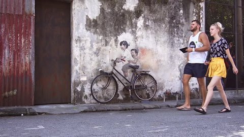 GEORGE TOWN. PENANG. MALAYSIA - CIRCA MAY 2017: Tourists in a rickshaw. passing a 3D mural in George Town. UltraHD 4k video