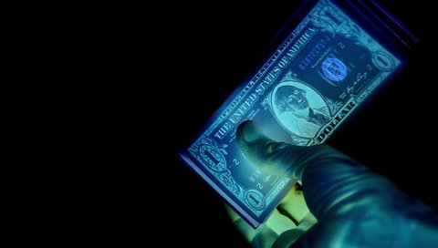 Paper dollars on black background, hold with fingers. Vivid, colors. IR like colors. Inspecting. Electronic money. Black money. Black market.