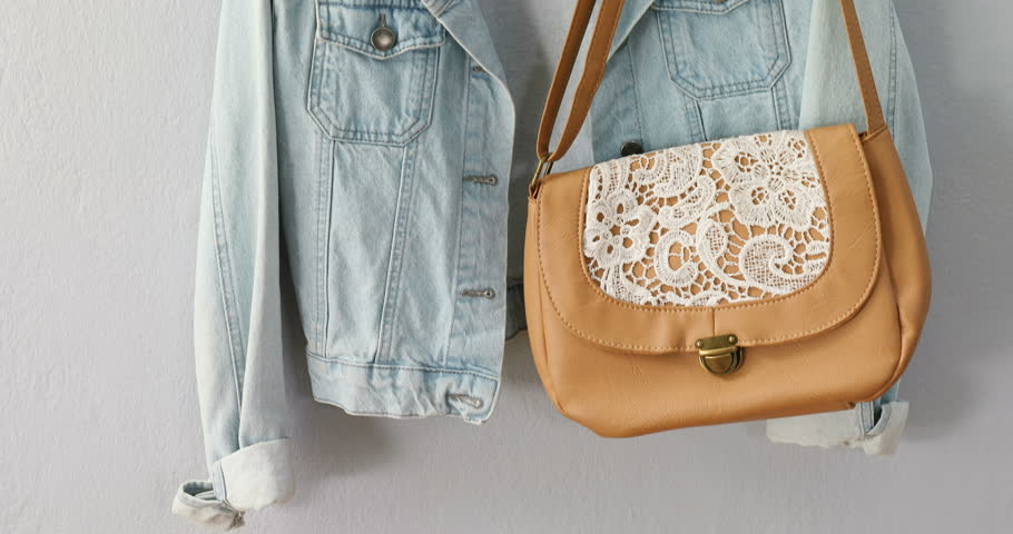 Close -up of denim jacket, purse, and woolly hat hanging hook 4k | Shutterstock HD Video #1009099586