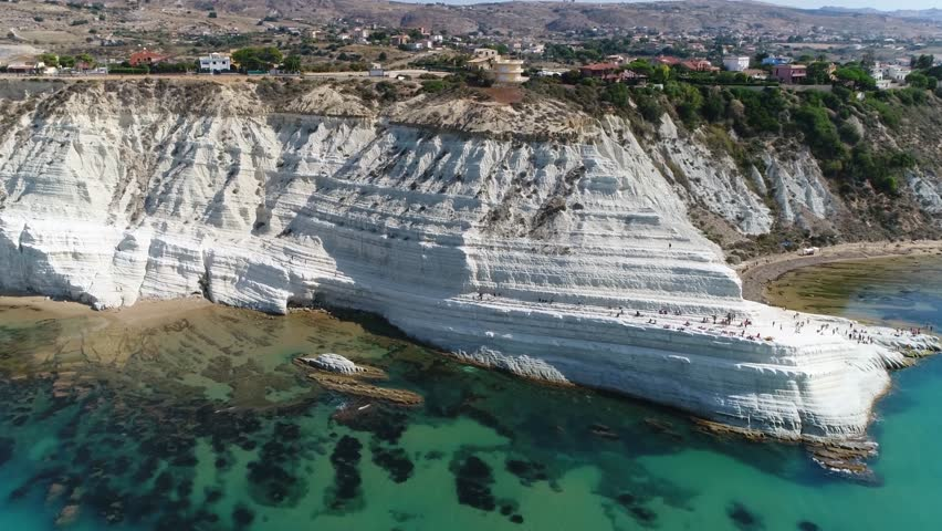 Aerial bird view flight towards Stair of the Turks in Italian Scala dei Turchi rocky cliff on coast of Realmonte near Porto Empedocle southern Sicily Italy it has become popular tourist attraction 4k
