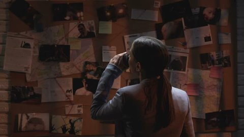 Lady private agent looking at crime investigation board, drinking cup of coffee