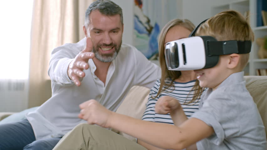 Medium shot of young woman laughing and watching middle-aged man playing with cute little boy in VR headset