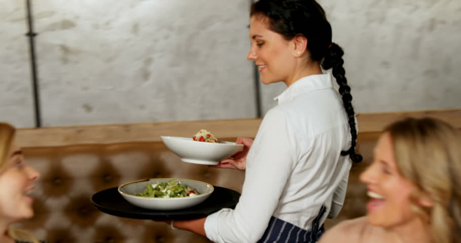 Waitress serving food to friends group in the restaurant 4K