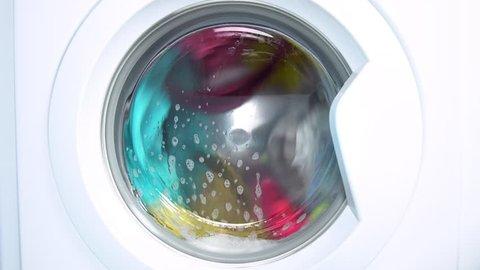 Washing machine washes colored clothing and sheets. Cylinder spinning. Nobody