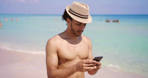Handsome cheerful man in hat showing shaka gesture and taking selfie with smartphone on beach at the ocean.