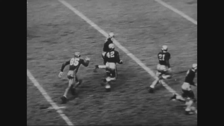 CIRCA 1940s - Two teams play American football on a stadium in front of a large audience in 1943.