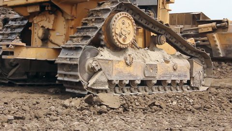 Heavy earth mover, bulldozer machine is leveling construction site. View on bulldozer, crawler while he is moving and leveling ground at building site.