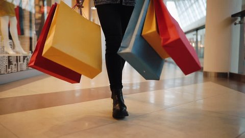 Young blonde woman walks with colorful shopping bags around a shopping mall