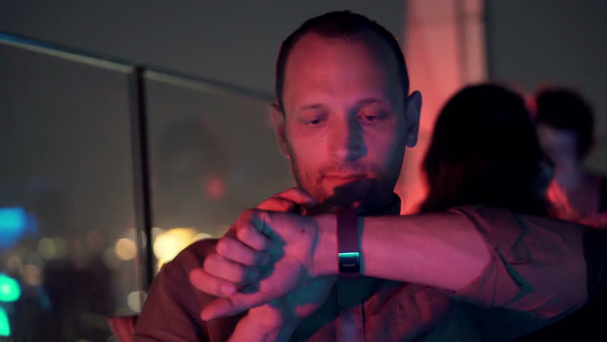 Young man using smartwatch while sitting on terrace in bar at night
