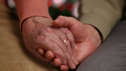 Senior hands of woman and man holding in front of christmas lights - old age concept, together forever, extreme closeup