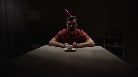 Lonely man lighting candle on birthday cupcake, sitting alone in dark room
