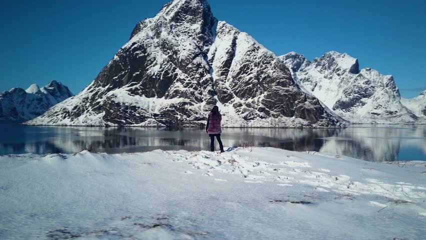 4k aerial drone footage - Woman admiring the snow covered mountains of Reine, Norway.  Lofoten Islands archipelago.