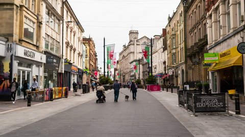 CARDIFF, UK - MAY 18, 2017: A hyperlapse of old central streets in Cardiff, Wales, UK with walking people on a cloudless spring day. Time-lapse during the day