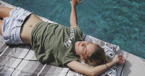 nice cute fit resting girl or woman relaxing near swimming pool, enjoying her time, holding and moving her hand in water, closing her eyes, wearing casual summer clothing