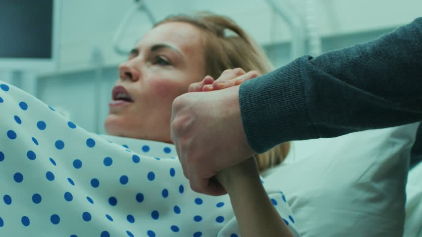 Close-up on a Face of a Woman in Labor Pushing Hard to Give Birth, Obstetricians Assisting, Spouse Holds Her Hand. Modern Maternity Hospital with Professional Midwives. Shot on RED EPIC-W 8K Camera.