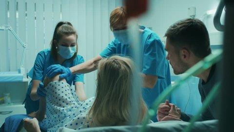 In the Hospital Woman in Labor Pushes to Give Birth, Obstetricians Assisting, Husband Holds Her Hand. Modern Delivery Ward with Professional Midwives. Back View Footage. Shot on RED EPIC-W 8K Camera.