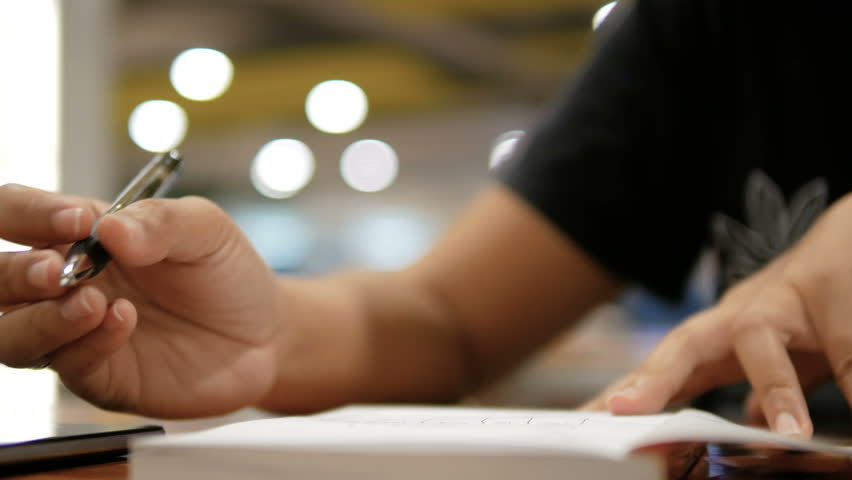 Close up shot hands of woman writing on paper notebook select focus shallow depth of field