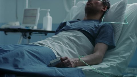 In the Hospital Sick Male Patient Sleeps on the Bed, Nurse Enters Medical Ward Checks His Vitals and Drop Counter. Sad and Blue Scene. Shot on RED EPIC-W 8K Helium Cinema Camera.