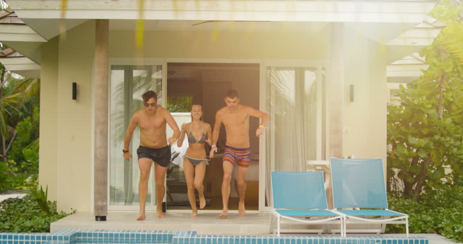 Three Young People Run out From Hotel Room and Jump into Small Swimming Pool with Splash. Teenagers Having Fun in Slow Motion. Shot on RED Epic 4K UHD Camera.