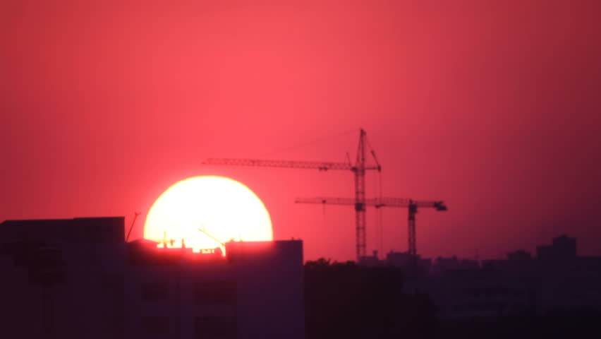 Silhouettes of two cranes in town at background bright sunrise sun in dawn sky
