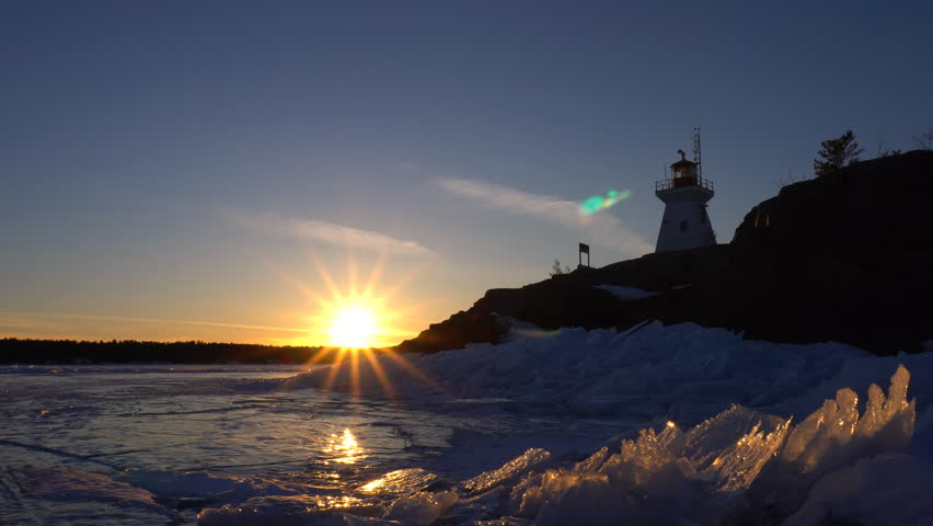 Sunset view of frozen lake and ice formations with lighthouse silhouette on rock shore in Killarney, Georgian Bay, Ontario, Canada
