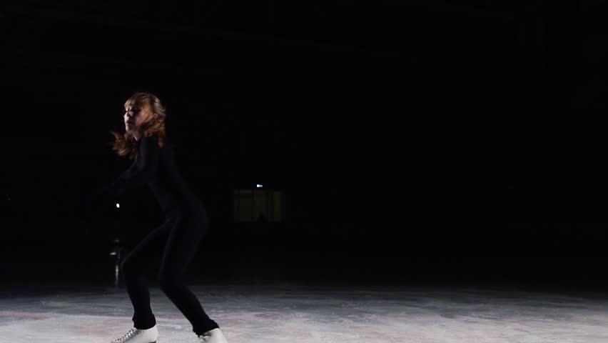 Skater in a black suit with a beautiful contour light accelerates and stops abruptly. Flying shards of ice from skates performs a jump with a triple turn. Rotation around its axis. Fall. Failure. A