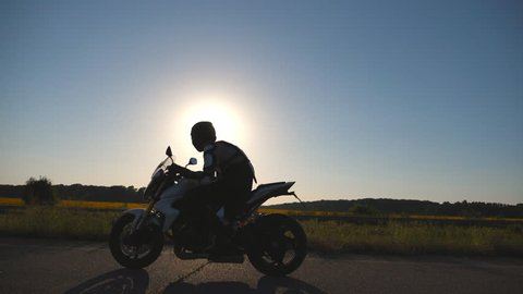 Man in helmet riding on a motorbike at highway with sun flares at background. Motorcyclist driving his motorcycle on country road during sunset. Slow motion Side view Close up