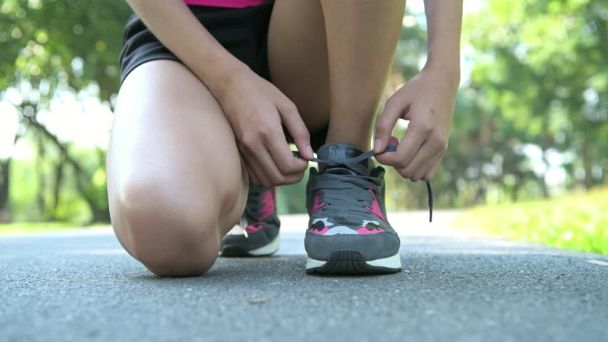 Woman prepare to run in park. Tying her shoe laces. Low angle shot. with copy space. | Shutterstock HD Video #1009415246