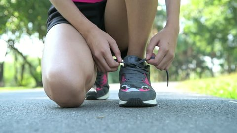 Woman prepare to run in park. Tying her shoe laces. Low angle shot. with copy space.
