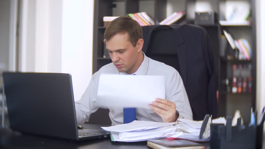 A businessman who scans documents, frowns, using a laptop, does not perform an urgent task in the office, there is not enough time, 4k. the office is hot, the air conditioning is not working