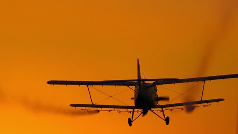 spray plane crop duster silhouette at sunset