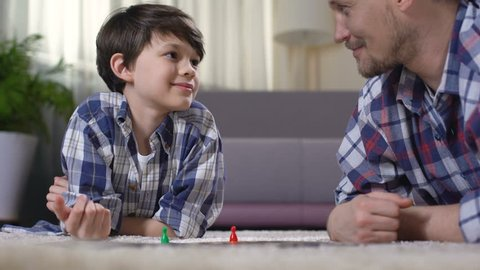 Father and son playing exciting board game, parent developing boys skills