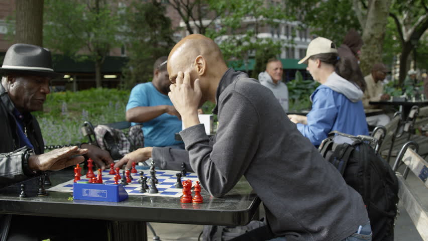 NEW YORK - MAY 17, 2015: panning, steadicam shot of chess tables with speed matches and timers in park in 4K slow motion Manhattan NY. Washington Square Park is a famous public park in NYC, USA.