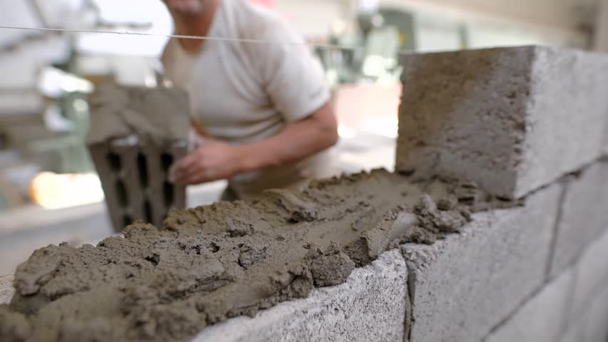 Close shot at the bricklayer's hands, the builder puts the bricks, using a stretched string for an even level of masonry materials | Shutterstock HD Video #1009470356