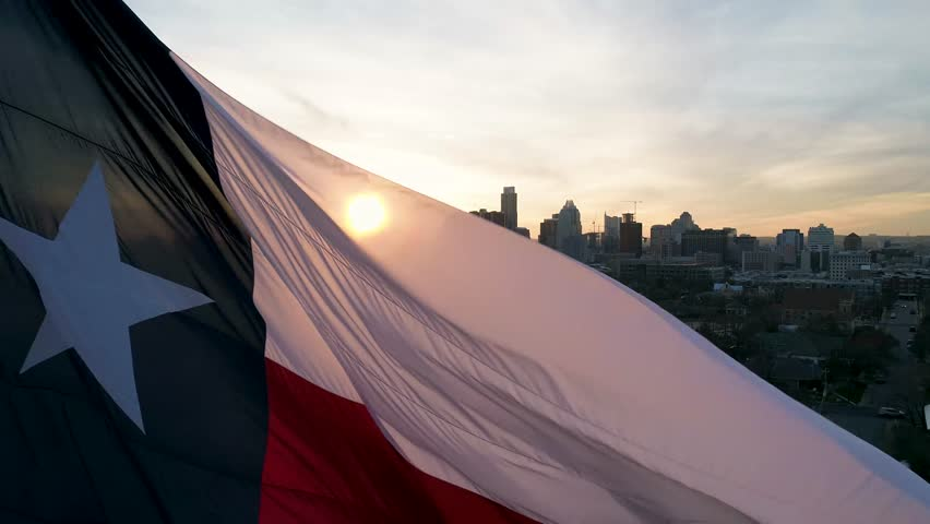 This is an orbiting aerial of a blowing Texas flag in Austin.