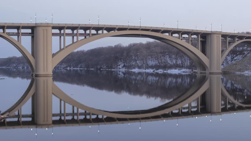A Wide Angle Shot of the New Franklin Bridge Spanning and Reflecting in a Calm Mississippi River during a Late Winter Dusk
