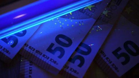 Counterfeit money detecting. Cheking euro banknotes with uv light.