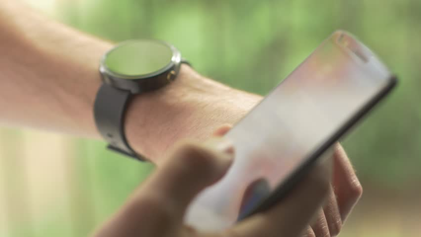 MONTREAL, CANADA - May 2015 Man hands gestures on a round screen modern smartwatch and a smartphone device. Connecting them togheter to be sync. Beautiful green exterior outdoor nature background bokeh.