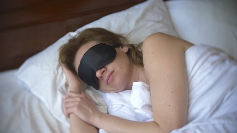 Young woman in a mask for sleeping, sleeping in bed on a pillow in the daytime. 4k.