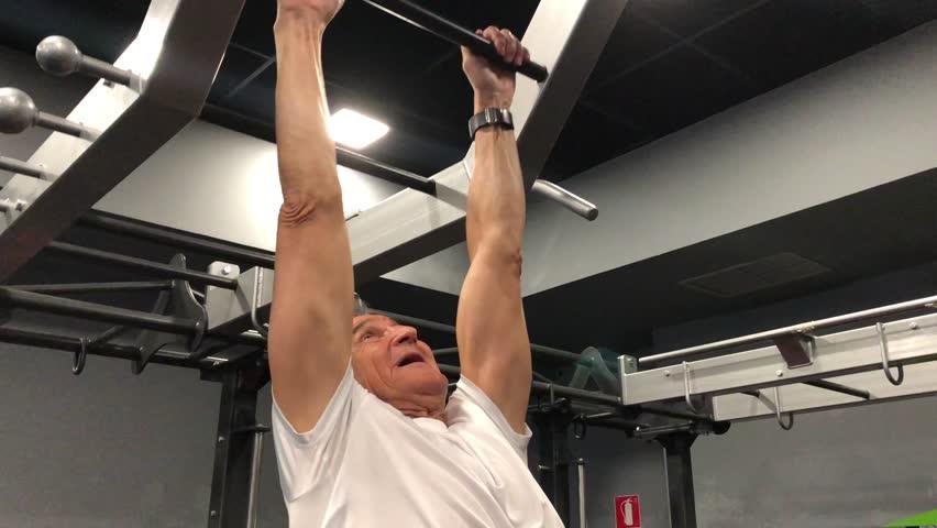Senior older man passes a ladder doing exercise.